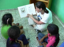 Lise Freking reads to the children after books were donated to the library
