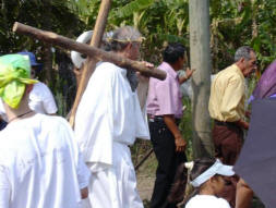 Mike Ruhland carries the cross during Stations of the Cross on Good Friday