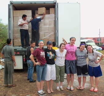 Heelan students help unload the containerof Then Feed Just One food that they helped to pack a month earlier